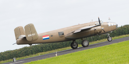 allies: LEEUWARDEN, THE NETHERLANDS - JUNE 10: WW2 B-25 Mitchell bomber in Dutch markings take off during the Dutch Air Force Open House. June 10, 2016 in Gilze-Rijen, The Netherlands