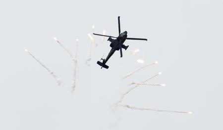 apache: LEEUWARDEN, THE NETHERLANDS - JUN 10, 2016: Dutch AH-64 Apache attack helicopter firing off flares during the Royal Netherlands Air Force Days Stock Photo