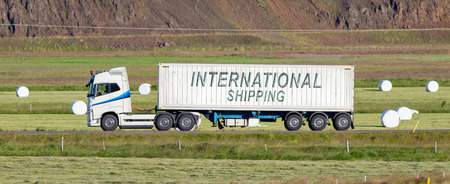 rural area: White trruck driving through a rural area - International shipping Stock Photo