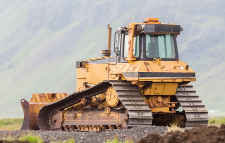 Yellow bulldozer in the field, construction in Iceland Stock Photo
