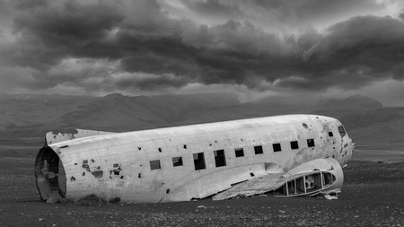 us military: The abandoned wreck of a US military plane on Solheimasandur beach near Vik, Southern Iceland - Stormy clouds Editorial