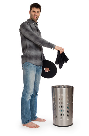 Young man putting dirty socks in a laundry basket, isolated on white
