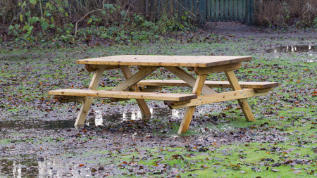 picknick: Wooden picknickplace on a green field in the rain Stock Photo
