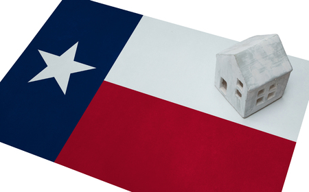 investment real state: Small house on a flag - Living or migrating to Texas Foto de archivo
