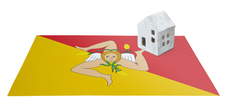 Small house on a flag - Living or migrating to Sicily Stock Photo