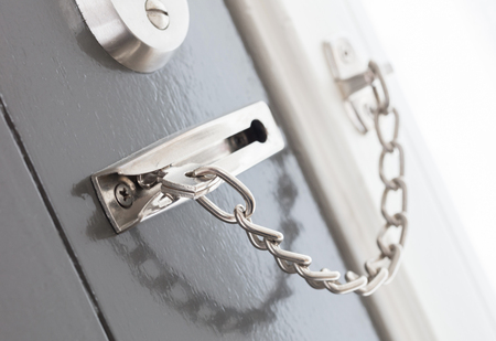 Door chain on a grey door, security measures Stock Photo
