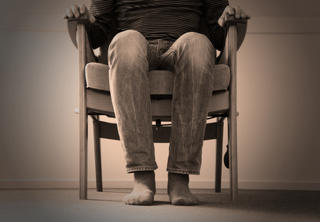evocative: Man sitting in armchair, slightly creepy setting Stock Photo