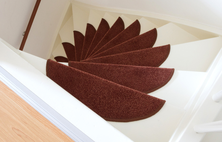 upstairs: White wooden stairs with red mats, going upstairs