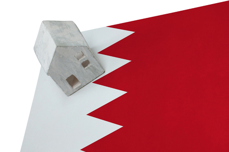 Small house on a flag - Living or migrating to Bahrain Stock Photo