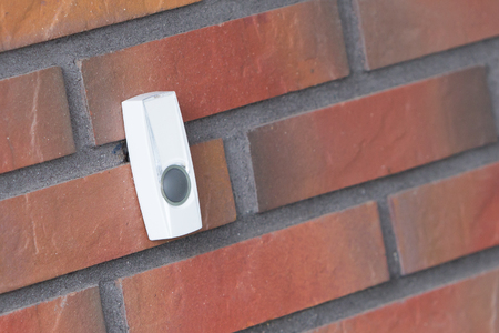 Simple doorbell on a brick wall, push to gain entrance