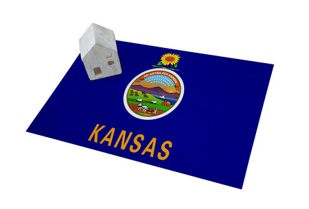 migrating: Small house on a flag - Living or migrating to Kansas Stock Photo