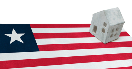 migrating: Small house on a flag - Living or migrating to Liberia Stock Photo