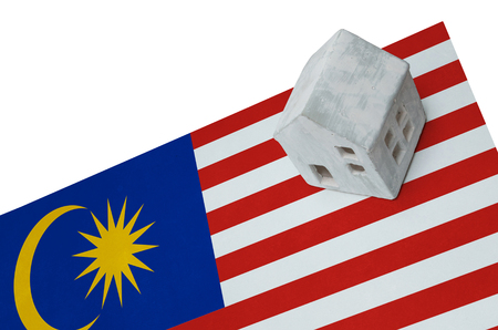 realestate: Small house on a flag - Living or migrating to Malaysia Stock Photo