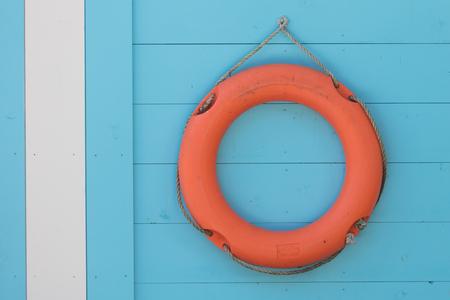 Red life buoy hanging at a lake