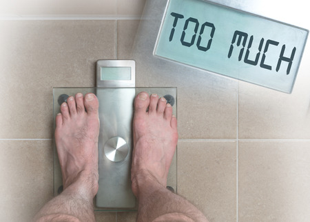 Closeup of mans feet on weight scale - Too much