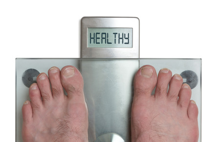 Closeup of mans feet on weight scale - Healthy