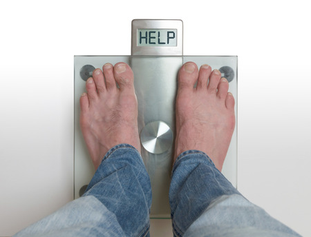 Closeup of mans feet on weight scale - Help Stock Photo