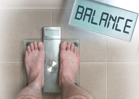 low section: Closeup of mans feet on weight scale - Balance