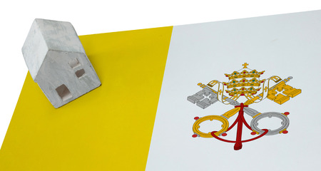 real estate house: Small house on a flag - Living or migrating to Vatican City Stock Photo