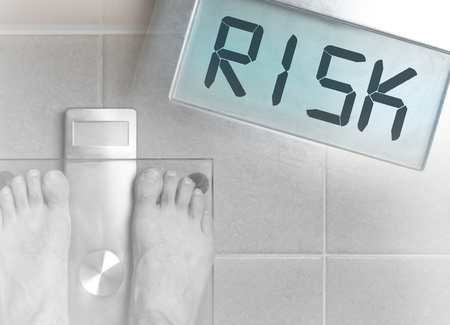 Closeup of mans feet on weight scale - Risk