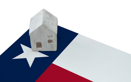 real estate house: Small house on a flag - Living or migrating to Texas Stock Photo