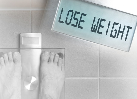 Closeup of mans feet on weight scale - Lose weight
