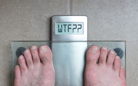 Closeup of mans feet on weight scale - WTF!!!
