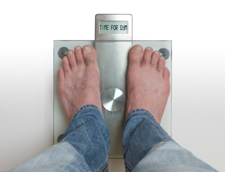 Closeup of mans feet on weight scale - Time for gym