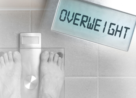 Closeup of mans feet on weight scale - Overweight Stock Photo