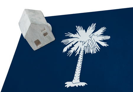 investment real state: Small house on a flag - Living or migrating to South Carolina Foto de archivo