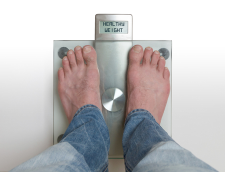 Closeup of mans feet on weight scale - Healthy weight