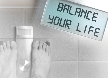 Closeup of mans feet on weight scale - Balance your life