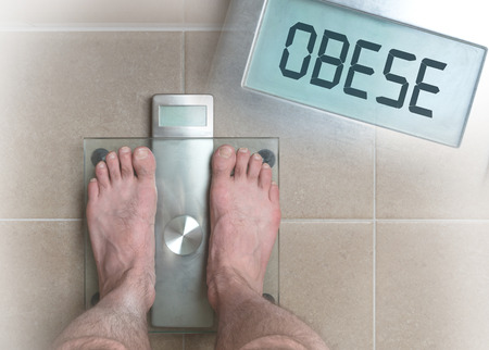 Closeup of mans feet on weight scale - Obese