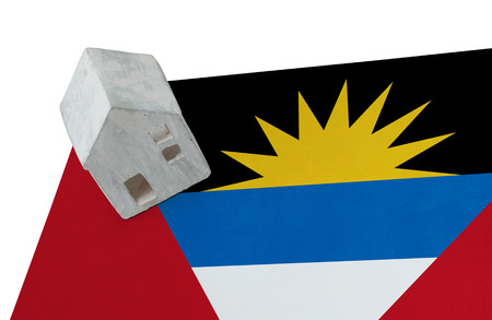 Small house on a flag - Living or migrating to Antigua and Barbuda Stock Photo