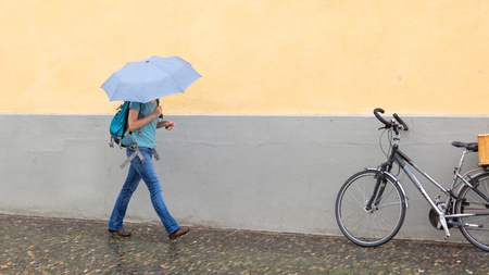Mysterious girl walking with umbrella on rainy day - Selective focus