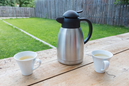 pitcher with two mugs in a garden