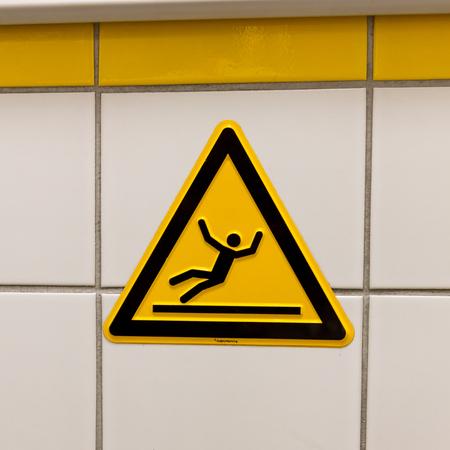 Warning sign for slippery floor - Tiled wall