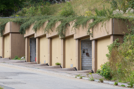 Doors of garages on a hill, empty street