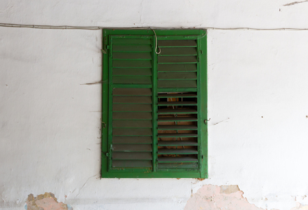 Green shutter on an old wall