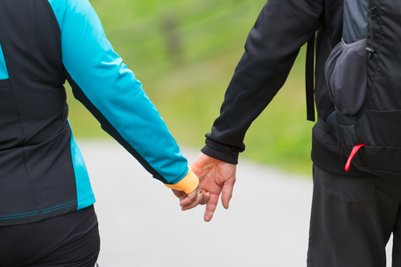 Old couple holding hands, selective focus - Hiking