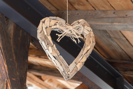 Decoration wooden heart hanging in a wooden house Banque d'images