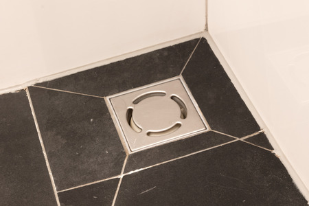 Metal drain hole in the tiled floor of a shower in bathroom