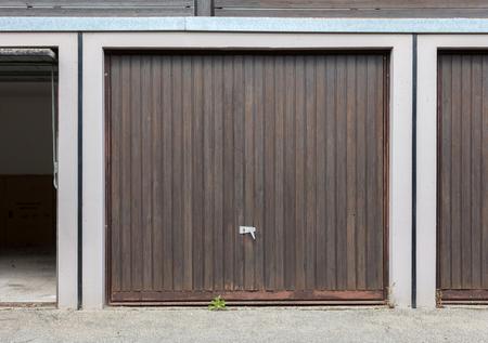 heavy industry: Old brown door of a garage, empty street