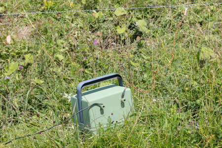 barbed wire fence: Green battery powering an electric fence - Austria