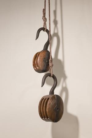 polea: Polea de madera vieja, aislada en una pared blanca Foto de archivo