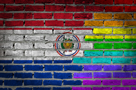 Very old dark red brick wall texture - Flag of Paraguay with rainbow flag