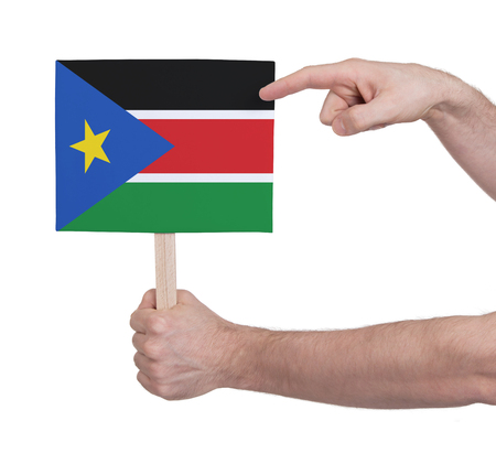 Hand holding small card, isolated on white - Flag of South Sudan