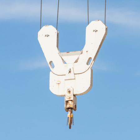 Vieux crochet de grue métallique sur fond de ciel bleu