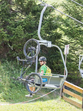 Nauders, Austria - August 4, 2017: Man with a mountainbike sitting in one of the many ski lifts in the Nauders area, summer sports.