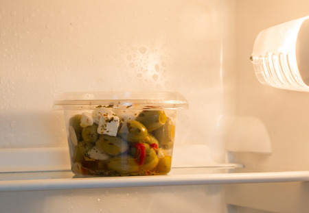 Olives in a refrigerator, selective focus on the olives Foto de archivo